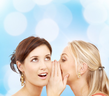 hearsay: friendship, happiness and people concept - two smiling young women whispering gossip