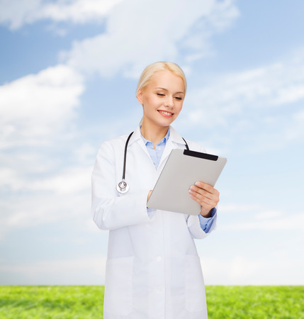 healthcare, technology and medicine concept - smiling female doctor with stethoscope and tablet pc computer photo