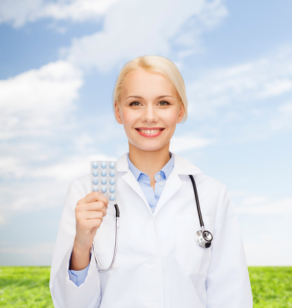healthcare, medicine and pharmacy concept - smiling female doctor and with pills and stethoscope photo