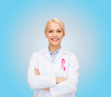 healthcare and medicine concept - smiling female doctor with pink cancer awareness ribbon over blue background photo