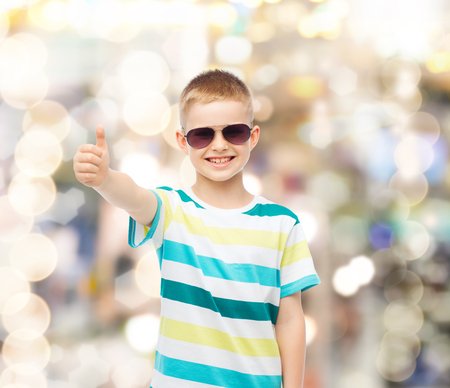 happiness, summer, gesture, childhood and people concept - smiling cute little boy in sunglasses over sparkling background showing thumbs up photo