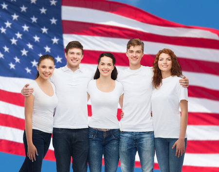 advertising, friendship, patriotism and people concept - group of smiling teenagers in white blank t-shirts over american flag background photo