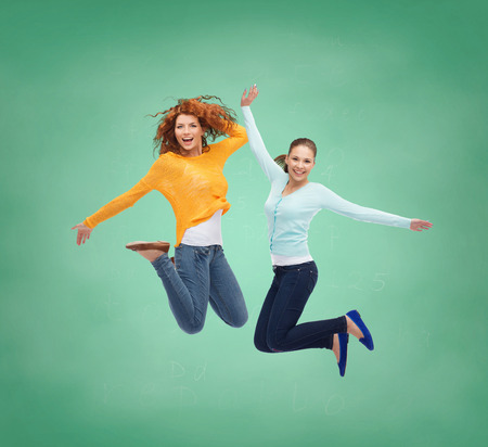 happiness, freedom, friendship, education and people concept - smiling young women jumping in air over green board background photo