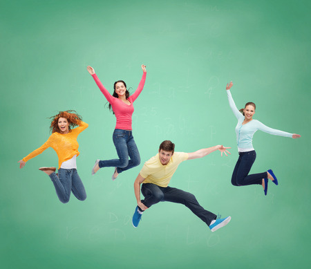happiness, freedom, friendship, education and people concept - group of smiling teenagers jumping in air over green board background photo