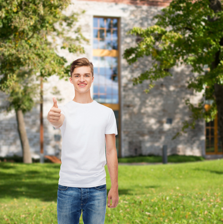approvement: gesture, advertising, summer vacation, education and people concept - smiling young man in blank white t-shirt showing thumbs up over campus background