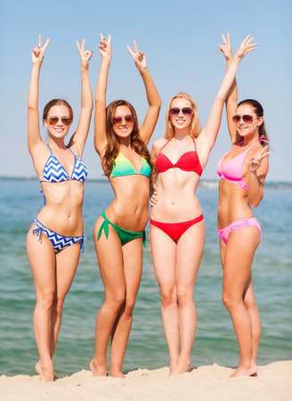summer vacation, holidays, gesture, travel and people concept - group of smiling young women showing peace or victory sign on beach Stock Photo