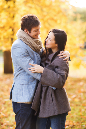 love, relationship, family and people concept - smiling couple hugging in autumn park photo