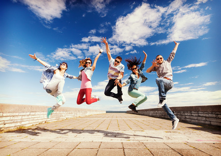 summer, sport, dancing and teenage lifestyle concept - group of teenagers jumping Standard-Bild