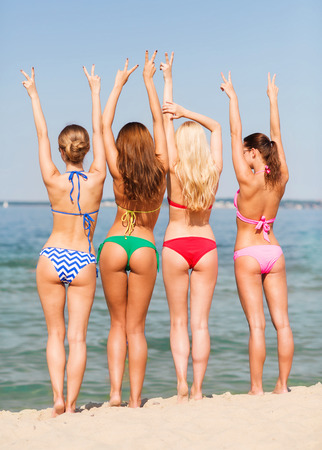 summer vacation, holidays, gesture, travel and people concept - group of young women showing peace or victory sign on beach from back Imagens