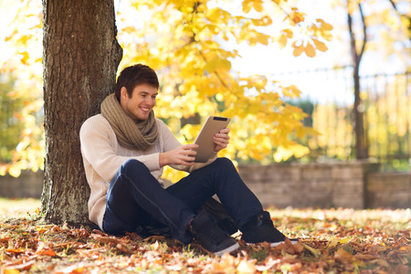 season, technology and people concept - smiling young man with tablet pc computer in autumn park photo