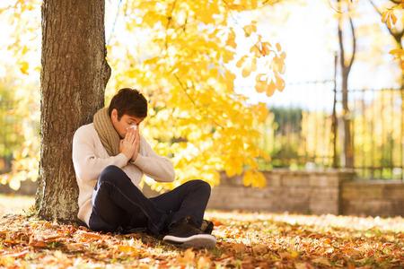 秋の公園でタブレット pc コンピューターと若い男の笑みを浮かべて - 季節、技術、人々 の概念 写真素材