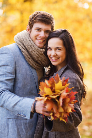 love, relationship, family and people concept - smiling couple with bunch of leaves hugging in autumn park photo