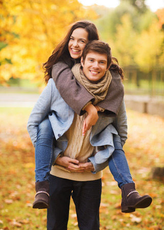 love, relationship, family and people concept - smiling couple hugging in autumn park Фото со стока