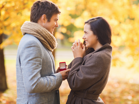 love, relationship, family and people concept - smiling couple with red gift box in autumn park photo