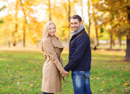 love, relationship, family and people concept - smiling couple holding hands in autumn park photo