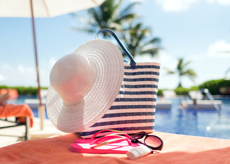 beach, summer and vacation and concept - close up of hat, bag, sunscreen and sunglasses at pool photo