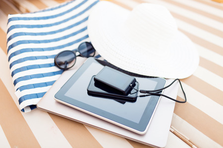 beach, summer vacations and technology concept - close up of tablet pc, notebook, smartphone and summer accessories on beach Stock Photo