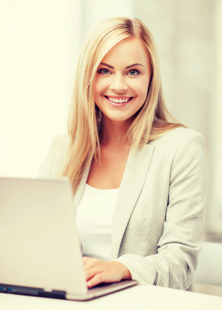 business and technology concept - businesswoman with laptop in office photo