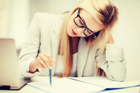business and education concept - indoor picture of bored and tired woman taking notes