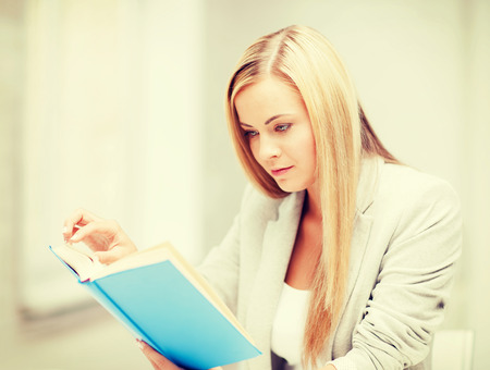 business, office, school and education concept - young woman reading book at school photo