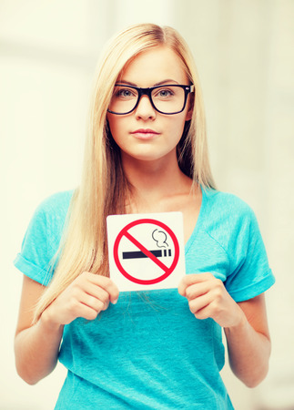 picture of woman with smoking restriction sign . photo