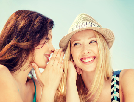 best friend: friendship, happiness and people concept - two smiling girls whispering gossip