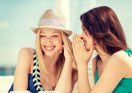 vacaciones de verano y concepto de vacaciones - muchachas de cotilleo en la cafetería en la playa