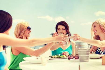 despedida de soltera: vacaciones de verano y concepto de vacaciones - niñas, haciendo un brindis en la cafetería en la playa