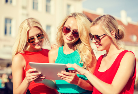 group picture: holidays and tourism concept - beautiful blonde girls toursits looking into tablet pc in the city Stock Photo