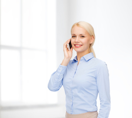 business, technology, internet and education concept - smiling young businesswoman with smartphone in white room photo