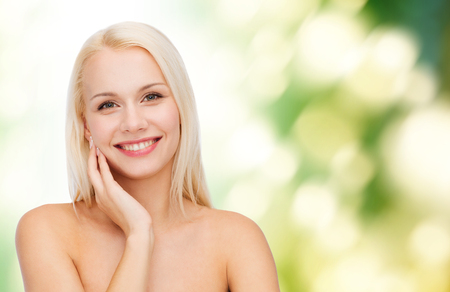 eco sensitive: health and beauty concept - smiling young woman touching her face skin