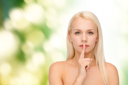 health and beauty concept - calm young woman with finger on lips photo
