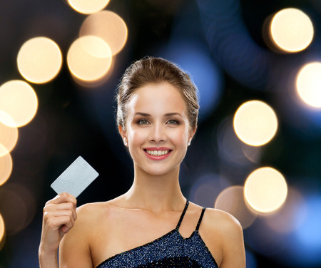 shopping, wealth, money, luxury and people concept - smiling woman in evening dress holding credit card over night lights background photo