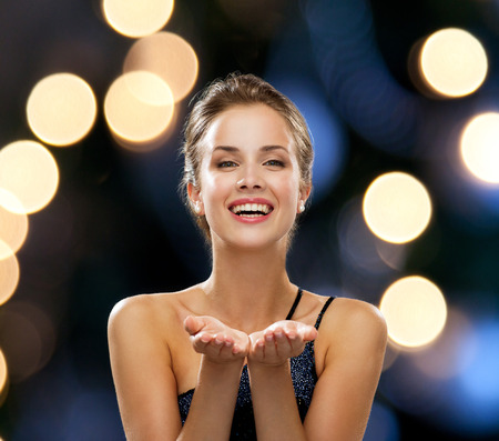people, holidays, advertisement and luxury concept - laughing woman in evening dress holding something imaginary over night lights background