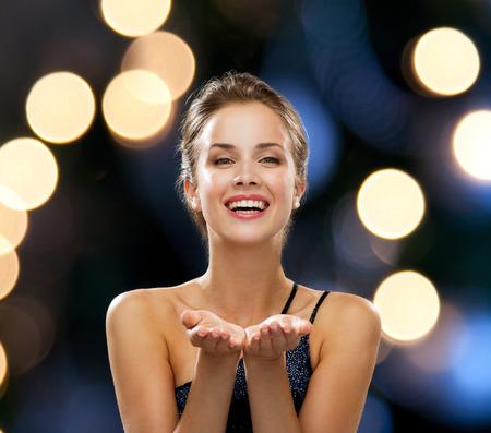 mensen, vakantie, reclame en luxe concept - lachende vrouw in avondjurk denkbeeldig iets over nacht lampjes achtergrond