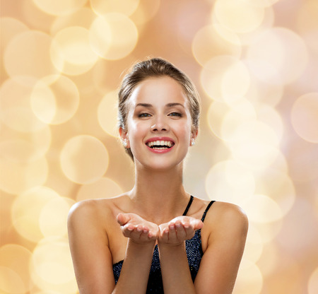 woman: people, holidays, advertisement and luxury concept - laughing woman in evening dress holding something imaginary over beige lights background