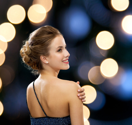 chic woman: people, holidays and glamour concept - smiling woman in evening dress over black background over night lights background from back