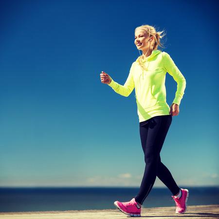 actief luisteren: fitness en lifestyle concept - vrouw lopen buiten Stockfoto