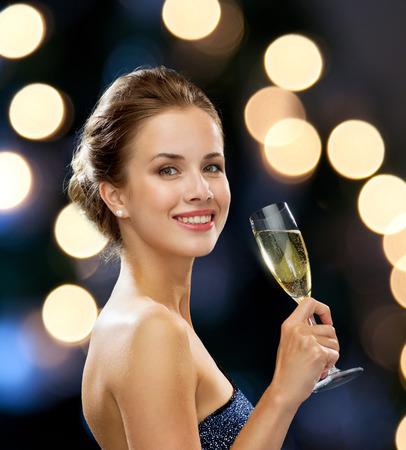 fiesta, bebidas, días de fiesta, lujo y celebración concepto - mujer sonriente en traje de noche con un vaso de vino espumoso en la noche las luces de fondo