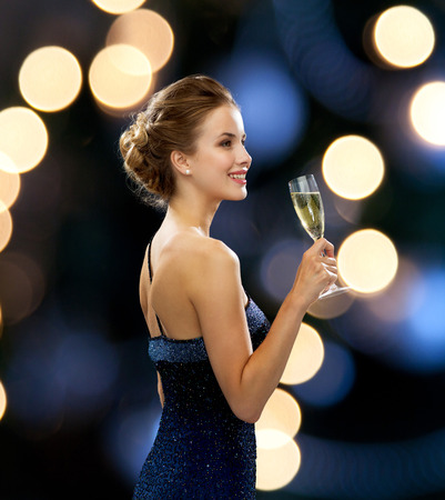 party, drinks, holidays, luxury and celebration concept - smiling woman in evening dress with glass of sparkling wine over night lights background Archivio Fotografico
