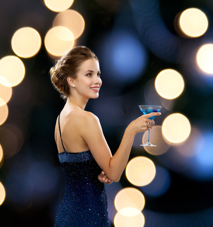 party, drinks, holidays, luxury and celebration concept - smiling woman in evening dress holding cocktail over night lights background photo