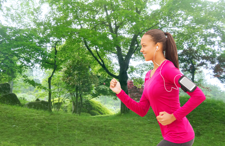 sport, fitness, health, technology and people concept - smiling young african american woman running with smartphone and earphones outdoors photo