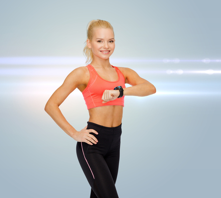 fitness, technology and exercising concept - smiling woman with heart rate monitor on hand photo