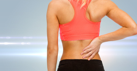 muscle pain: fitness, healthcare and medicine concept - close up of sporty woman touching her back