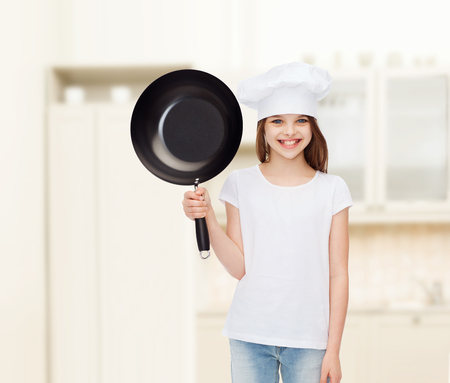 advertising, childhood, cooking and people - smiling girl in white t-shirt and cooking hat holding pan over blue background photo