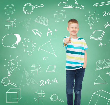 happiness, school, education, gesture and people concept - smiling boy pointing his finger at you over green board with doodles background photo