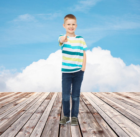happiness, childhood, gesture, summer and people concept - smiling boy pointing finger at you over blue sky and wooden floor background photo