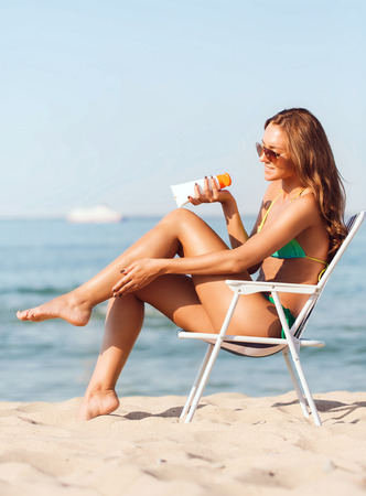 tanned girl: summer vacation, holidays and people concept - smiling young woman sunbathing in lounge on beach