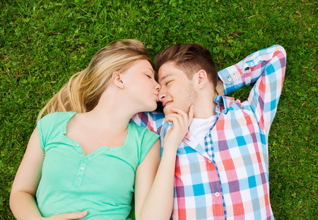 holidays, vacation, love and friendship concept - smiling couple lying on on grass and kissing in park photo