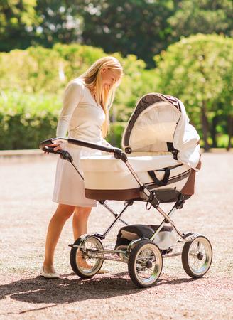 La familia, el niño y el concepto paternidad - madre feliz con el cochecito en el parque Foto de archivo - 31158757